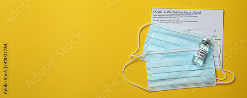 Canvas Print Vaccination record card, vaccine and masks on yellow background