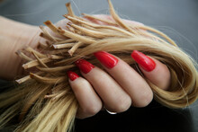 Encapsulated Strands Of Blonde Hair In Women's Hands With A Bright Red Manicure. The Concept Of Hair Care And Extension.