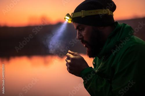 Hiker with headlamp warming up hands in evening Wallpaper Mural