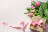 Fototapeta Tulips - Gift box with long pink ribbon and tulips on light background