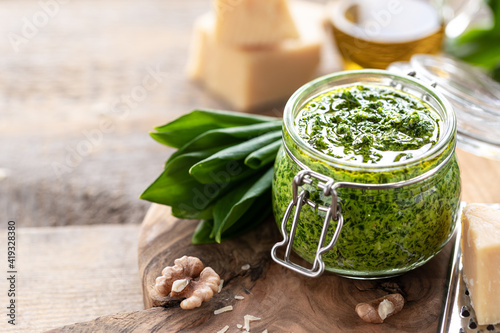 Fotografie, Obraz Wild leek pesto with olive oil and parmesan cheese in a glass jar on a wooden table