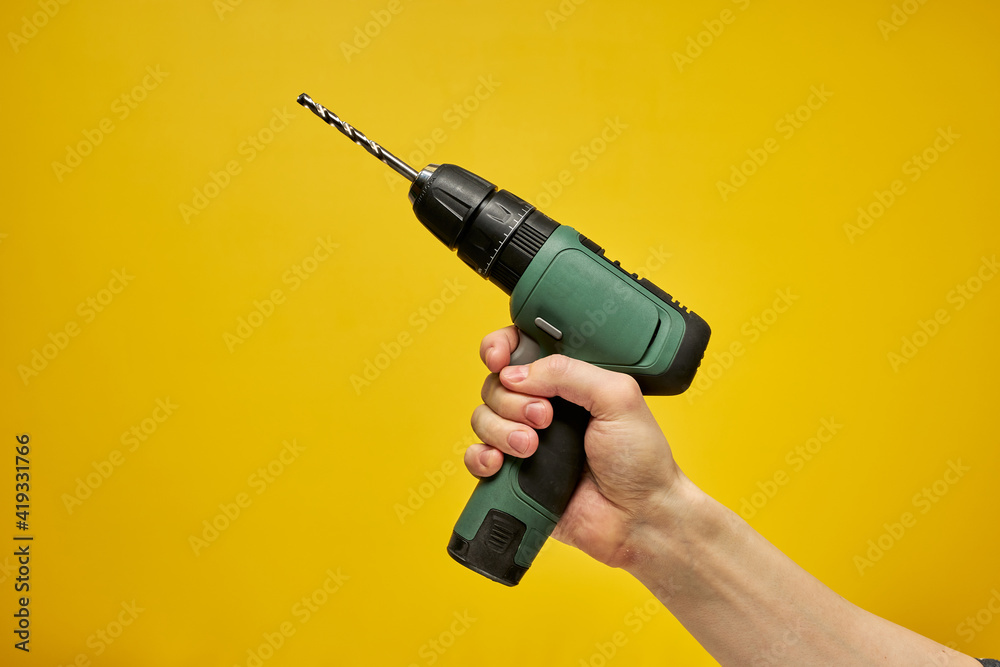 Fototapeta Green cordless battery powered drill on yellow background, cropped male hands holding tool for repair and building construction. copy space for advertisement