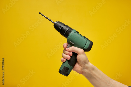 Fototapeta Green cordless battery powered drill on yellow background, cropped male hands holding tool for repair and building construction. copy space for advertisement obraz