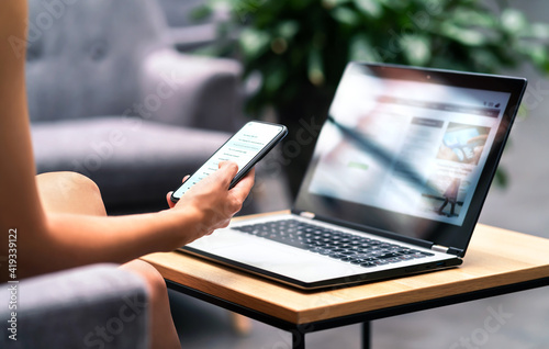 Wireless wifi for remote work in airport lounge bar, hotel lobby or cafe. Phone and laptop. Woman using smartphone and modern notebook pc computer on table. Real estate agent or student reading email.