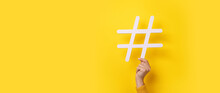 Hand Showing HASHTAG Over Yellow Background, Business Concept, Panoramic Mock-up