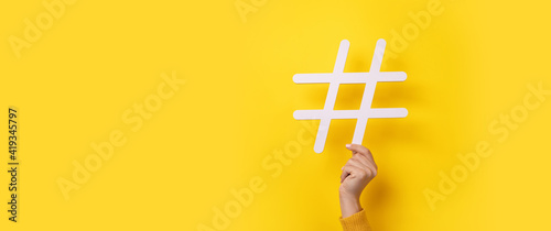 Photo hand showing HASHTAG over yellow background, business concept, panoramic mock-up