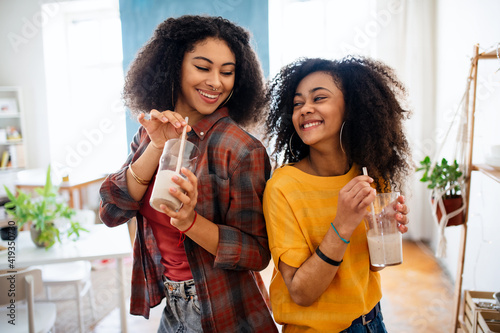 Portrait of young sisters indoors at home, drinking smoothie. Wallpaper Mural
