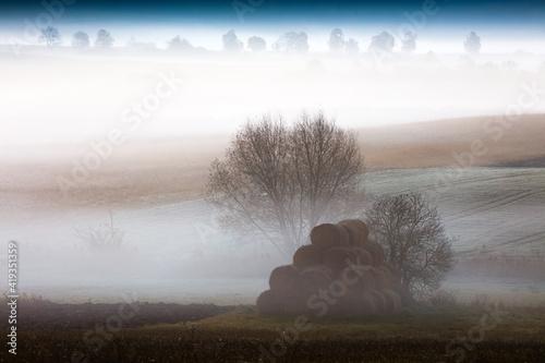 Obraz jesienny  mglisty świt  z belami siana - fototapety do salonu