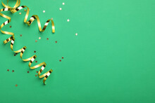Shiny Golden Serpentine Streamers And Confetti On Green Background, Flat Lay. Space For Text