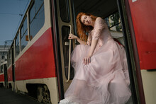 Pretty Red-haired Young Woman In Retro Style Fancy Prom Pink Dress Sitting On Steps Of Old Old Red Soviet Tram. Looking Inquiringly Arrogantly Asking At Camera. Young Rebel Spirit. Bright Sunlight