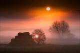 jesienny  mglisty świt  z belami siana i wschodem słońca