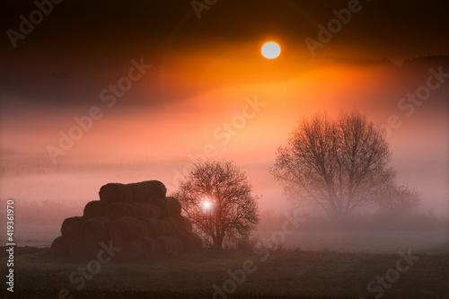 Obraz jesienny  mglisty świt  z belami siana i wschodem słońca - fototapety do salonu
