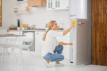Cute Blonde Housewife Cleaning The Fridge And Looking Busy
