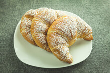 Three Croissants On A White Plate For Breakfast