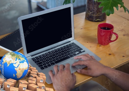 Composition of globe with cardboard boxes over man using laptop