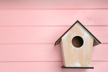 Beautiful Bird House On Pink Wooden Background, Space For Text