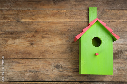 Canvas Beautiful green bird house on wooden background, space for text