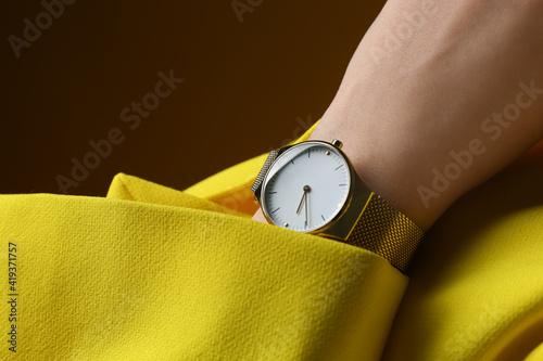 Canvas-taulu Woman wearing luxury wristwatch on brown background, closeup