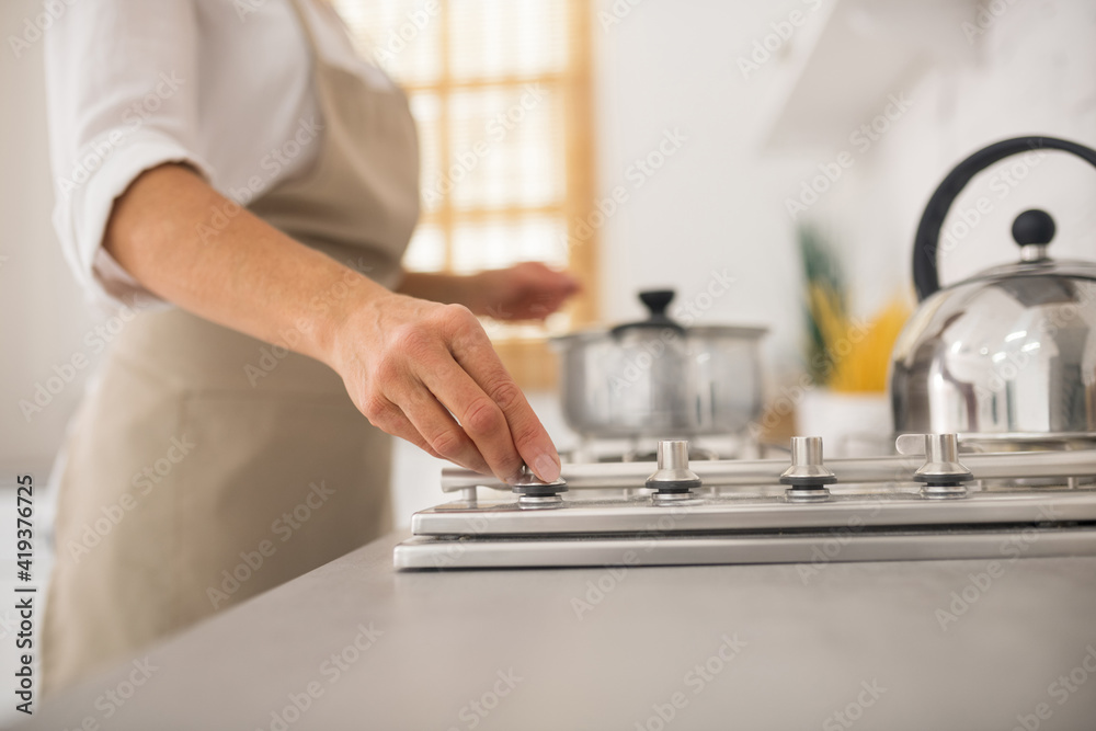 Fototapeta Housewife in apron cooking in the kitchen