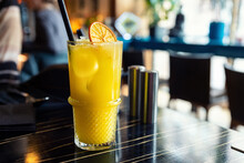 Glass With Tasty Juicy Bright Yellow Citrus Orange Lemonade Cocktail On Dark Wooden Table At Cafe Or Restaurant On Brigh Sunny Morning Day. Nonalcoholic Party Drink. Hipster Lifestyle Background