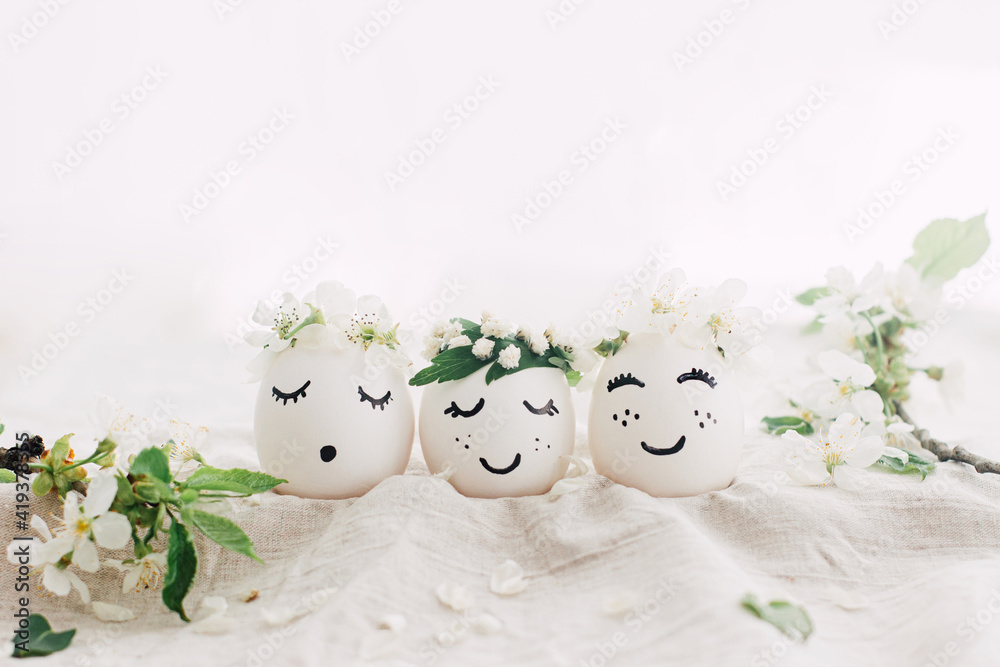 Fototapeta Natural easter eggs with drawn cute faces in floral wreaths on linen fabric with bloom in light
