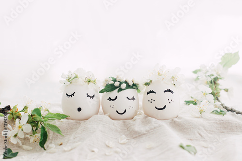 Obraz Natural easter eggs with drawn cute faces in floral wreaths on linen fabric with bloom in light - fototapety do salonu