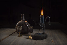 An Old Dusty Bottle Of Dark Brown Bottle With Alcohol, Two Goblet And A Metal Candlestick Holder With A Candle On A Wooden Table On A Dark Background.