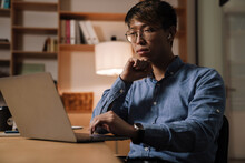 Focused Asian Guy Working With Laptop While Sitting At Table In Office