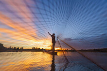 Silhouette Of A Fisherman Standing In A Boat Casting A Fishing Net At Sunset, Thailand