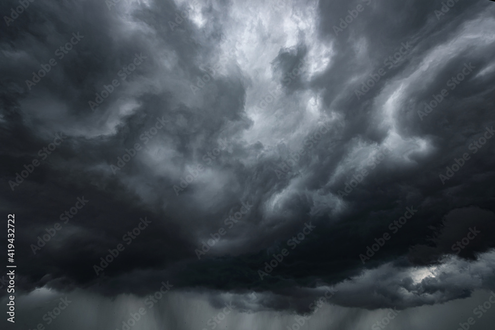 Fototapeta Rain and dark rain clouds. Stormy dark sky with black clouds and a strong wind. Panoramic view. Concept on the theme of weather, natural disasters, rainstorm, thunderstorm.