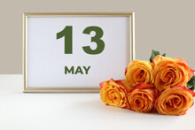 Day Of The Month 13 May Calendar Photo Frame And Yellow Rose On A White Table