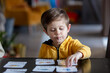 little boy learns words from cards under the ABA therapy program at home at the table