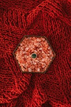 From Above Of Gold Ring With Green Gemstone Placed In Box With Pink Decoration Stones Placed On Red Fabric During Wedding Celebration