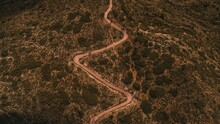 Drone View Of Narrow Winding Rural Roadway Going Through Mountainous Land With Green Trees And Shrubs In Nature In Countryside