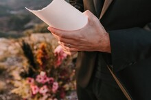 Unrecognizable Fiance Wearing Black Suit Standing With Paper During Wedding Vow In Nature Against Colorful Bouquets Of Flowers On Blurred Background