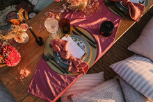 Top View Of Wooden Table With Envelope And Napkin Placed On Plate Near Cutlery And Colorful Flowers On Street In Sunlight