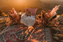 Pink Armchair With Flowers On Fluffy Plaid Placed On Vintage Rug With Decorative Feathers On Hilltop In Nature During Wedding Celebration