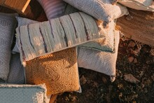 Top View Stack Of Various Cushions With Colorful Knitted Pillowcases Placed On Ground In Countryside In Sunlight In Rural Terrain