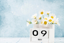 White Cube Calendar For May Decorated With Daisy Flowers Over Blue With Copy Space