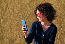 Charming Asian Female With Afro Hairstyle Taking Photo On Selfie Camera Of Smartphone On Background Of Yellow Wall Of Building On Sunny Day