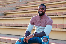 Positive African American Male In Stylish Outfit Sitting On Stone Steps On Street And Looking At Camera