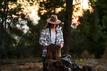 Front View Serene Young Female In Casual Wear And Hat Hunkering Down And Opening Backpack While Having Break In Verdant Woods At Sunset