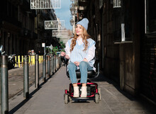 Young Contemplative Female In Stylish Clothes Looking Away While Sitting In Electric Wheelchair Driving On Urban Pavement In Daylight