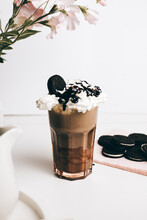 Sweet Yummy Frappe Drink With Chocolate Cookies On Whipped Cream In Light Kitchen