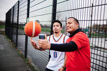 Latino Friends Taking A Selfie By The Fence Of A Basketball Court Outdoors.