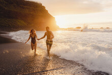 Full Length Of Happy Young Couple In Swimwear Holding Hands And Walking Together In Waving Sea Water At Sunset Time While Enjoying Holidays On Tenerife Island In Spain