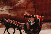 Unrecognizable Young Ethnic Male Tourist In Elegant Outfit Standing Near Horse Carriage In Sandstone Canyon In Petra