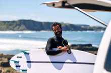 Adult Man In Wetsuit With Surfboard Smiling Happily Standing On Seashore Against Hills