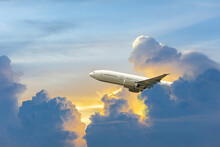 Side Image Commercial Passenger Aircraft Or Cargo Transportation Airplane Flying Through Over Fluffy Cloudy With Blue Sky And Yellow Sunshine Near Dusk