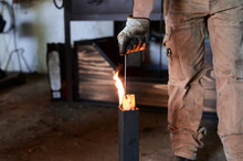 Crop Anonymous Tattooed Male Blacksmith In Casual Clothes And Apron Heating Metal Pliers In Flame During Forging Process In Workshop